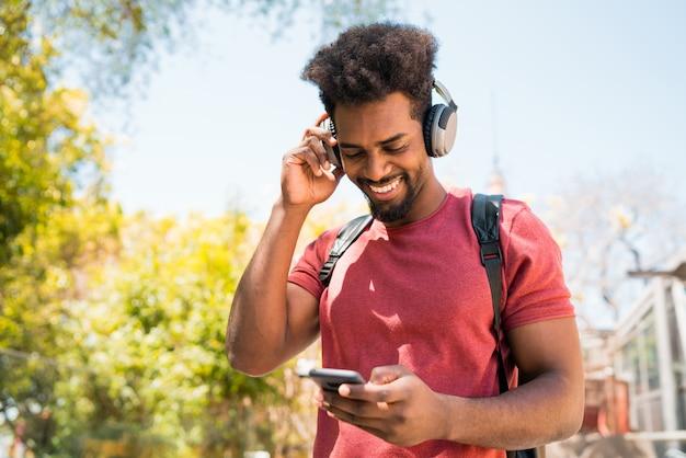 Junger afro-mann, der musik mit seinem handy hört.