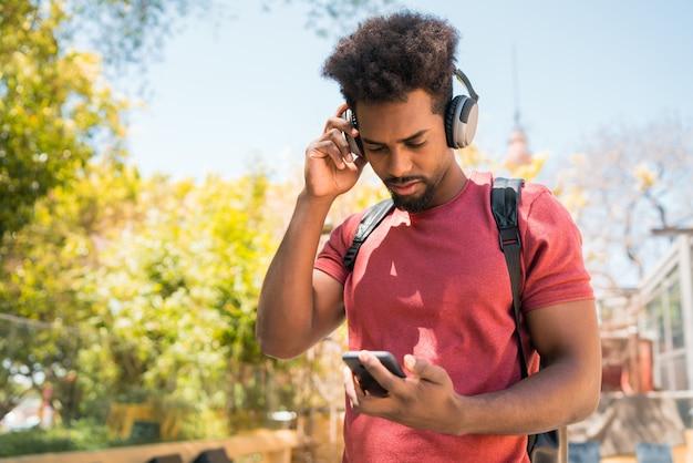 Junger afro-mann, der musik mit seinem handy hört