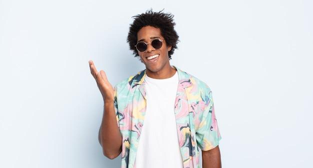 Junger afro-mann, der sich glücklich, überrascht und fröhlich fühlt, mit positiver einstellung lächelt und eine lösung oder idee verwirklicht
