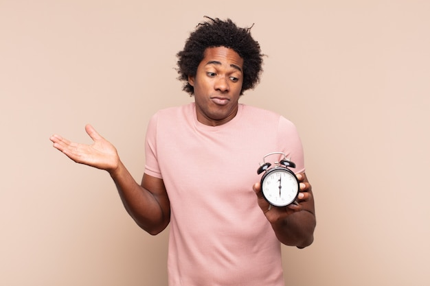 Junger afro-mann, der sich verwirrt und verwirrt fühlt, zweifelt, gewichtet oder verschiedene optionen mit lustigem ausdruck wählt