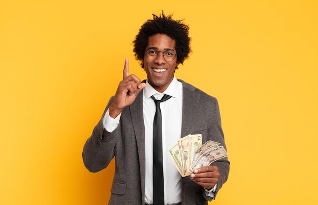 Junger afro-mann, der sich wie ein fröhliches und aufgeregtes genie fühlt, nachdem er eine idee verwirklicht hat und fröhlich den finger hebt, eureka!