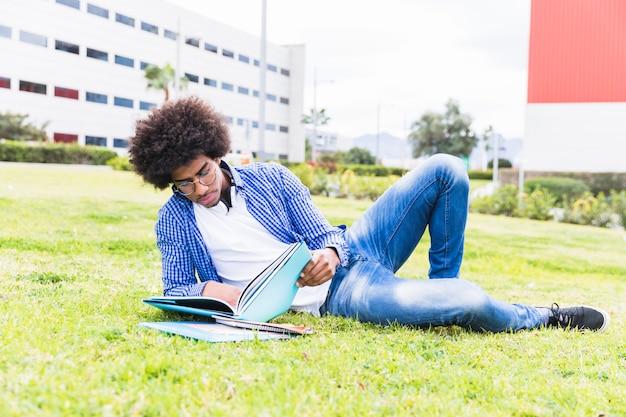 Junger afroafrikanischer männlicher student, der auf das grüne gras liest das buch legt