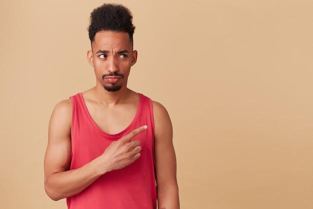 Junger afroamerikaner, bärtiger kerl mit afro-frisur. trage ein rotes trägershirt. ernsthaft beobachten und mit dem zeigefinger nach rechts auf den kopierraum zeigen, isoliert über pastellbeige wand