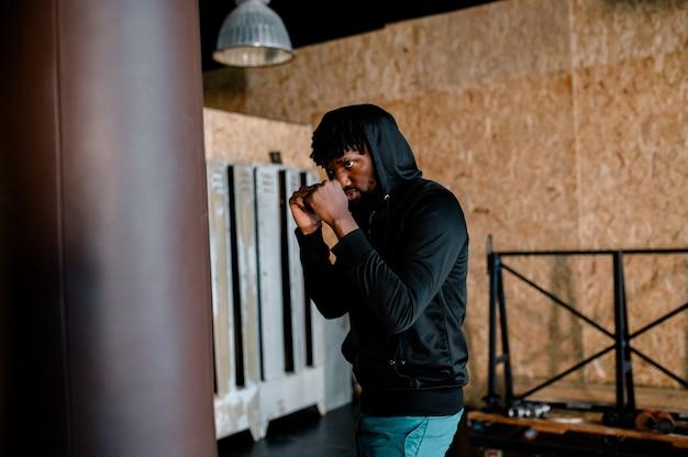 Junger afroamerikaner-boxer, der an einer turnhalle trainiert
