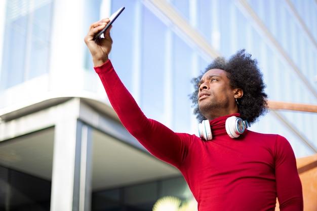 Junger afroamerikaner, der ein foto von sich selbst mit einem smartphone macht. er ist draußen neben einem modernen gebäude. platz für text.