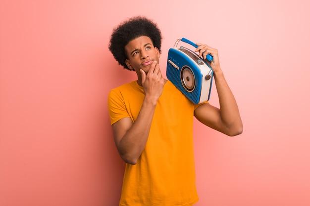 Junger afroamerikaner, der ein vintage-radio hält, das zweifelt und verwirrt