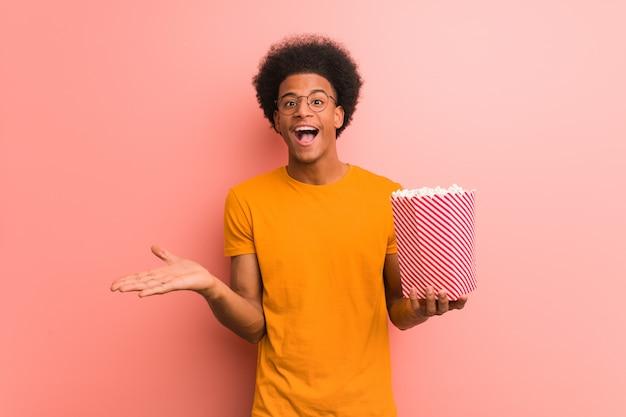 Junger afroamerikaner, der einen popcorneimer feiert einen sieg oder einen erfolg hält