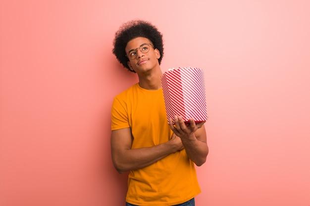 Junger afroamerikaner, der einen popcorneimer lächelt überzeugt und die arme kreuzt und oben schaut hält