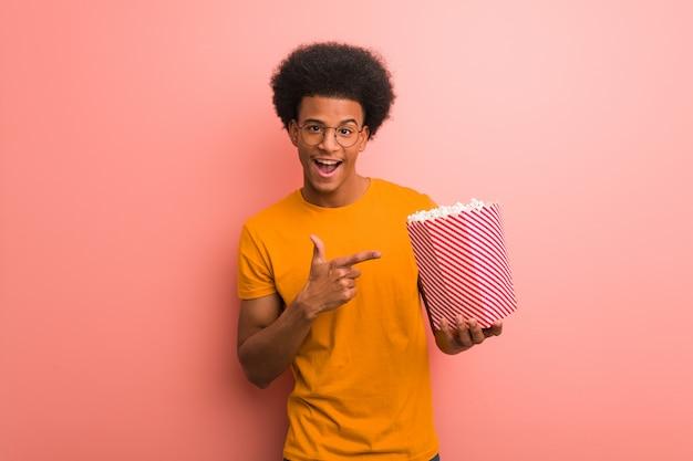 Junger afroamerikaner, der einen popcorneimer zeigt auf die seite mit dem finger hält