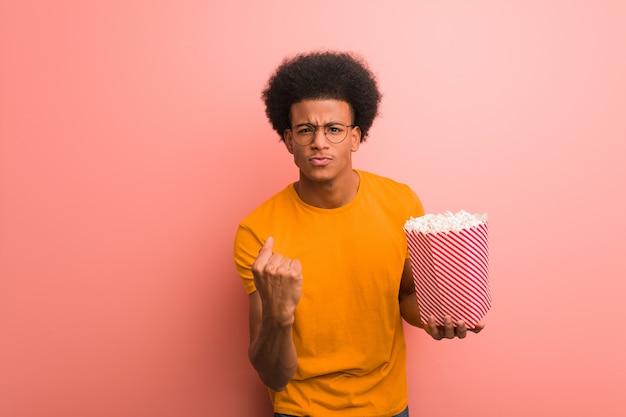 Junger afroamerikaner, der einen popcorneimer zeigt faust zur front, verärgerter ausdruck hält