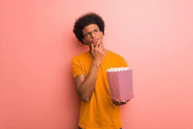 Junger afroamerikaner, der einen popcorneimer zweifelnd und verwirrt hält