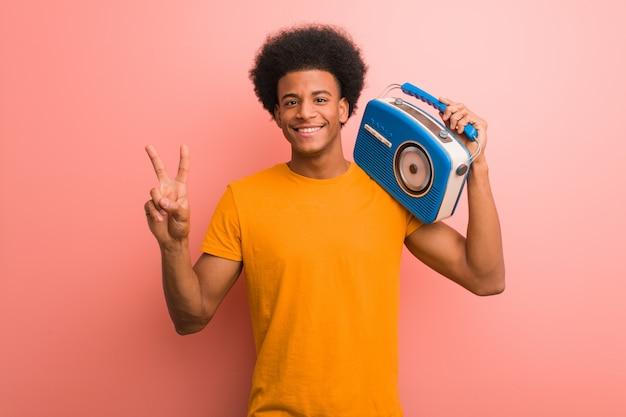 Junger afroamerikaner, der einen weinleseradio zeigt nummer zwei hält