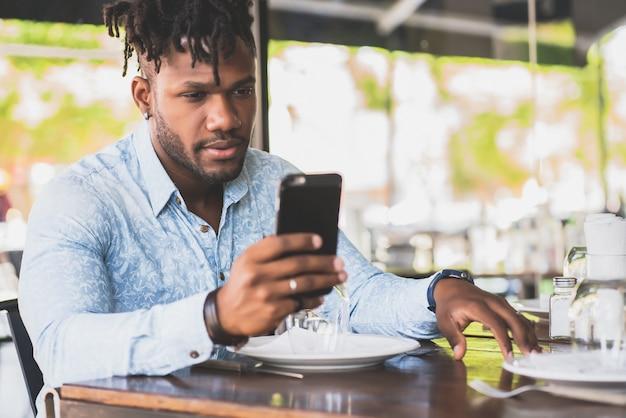Junger afroamerikaner, der sein handy benutzt, während er in einem restaurant sitzt.