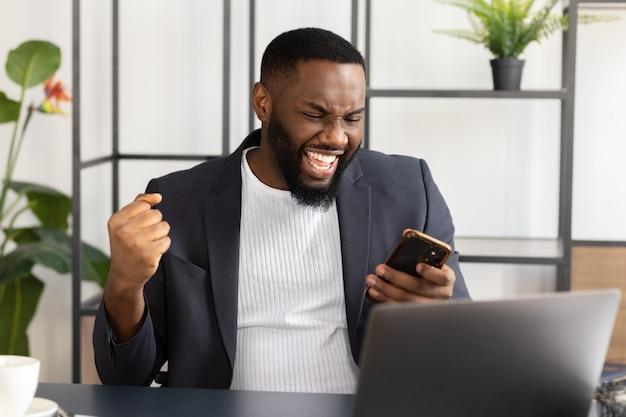 Junger afroamerikaner, der unerwartet gute nachrichten auf dem smartphone liest