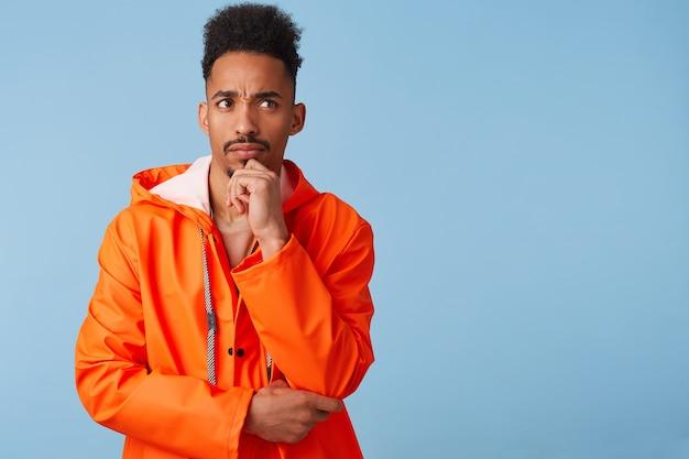 Junger afroamerikaner im orangefarbenen regenmantel denkt an etwas wichtiges, berührt sein kinn, schaut weg und steht mit kopierraum.