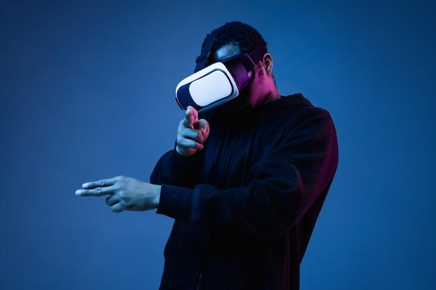 Junger afroamerikaner in vr-brille in neon auf blauem hintergrund. männerporträt