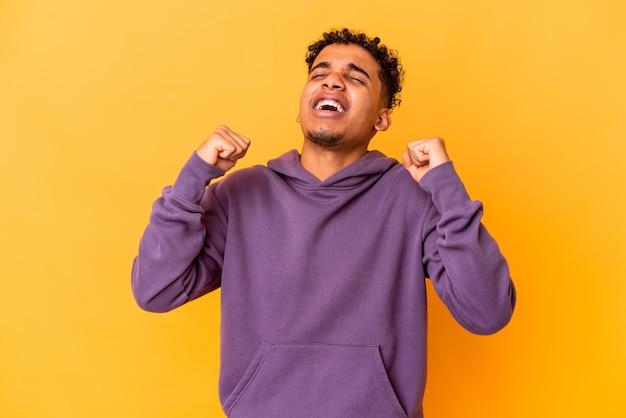 Junger afroamerikaner lockiger mann auf gelb, der einen sieg, leidenschaft und begeisterung, glücklichen ausdruck feiert.