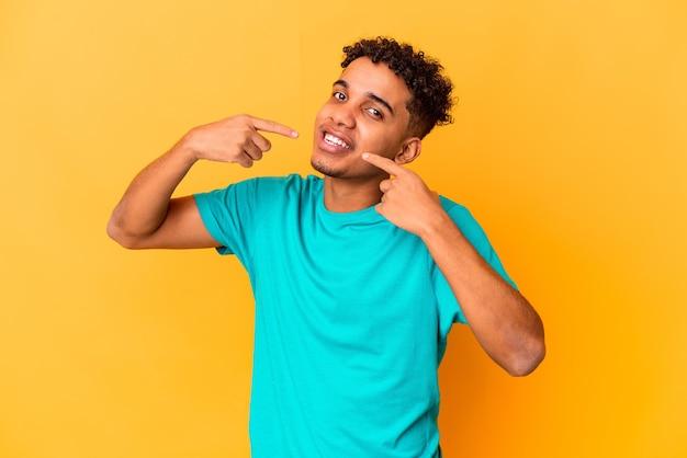 Junger afroamerikaner lockiger mann auf lila lächelt und zeigt finger auf mund.