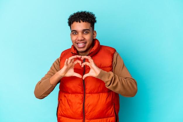 Junger afroamerikaner lockiger mann lokalisiert auf blau lächelnd und zeigt eine herzform mit händen.