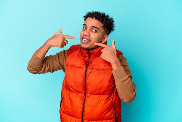 Junger afroamerikaner lockiger mann lokalisiert auf blauem lächeln, finger auf mund zeigend.