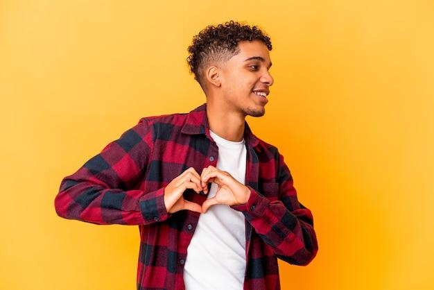 Junger afroamerikaner lockiger mann lokalisiert auf lila lächelnd und zeigt eine herzform mit händen.