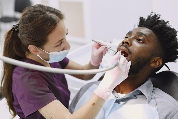 Junger afroamerikaner. mann besucht zahnarztpraxis zur vorbeugung der mundhöhle. mann und familienarzt während der kontrollzähne.