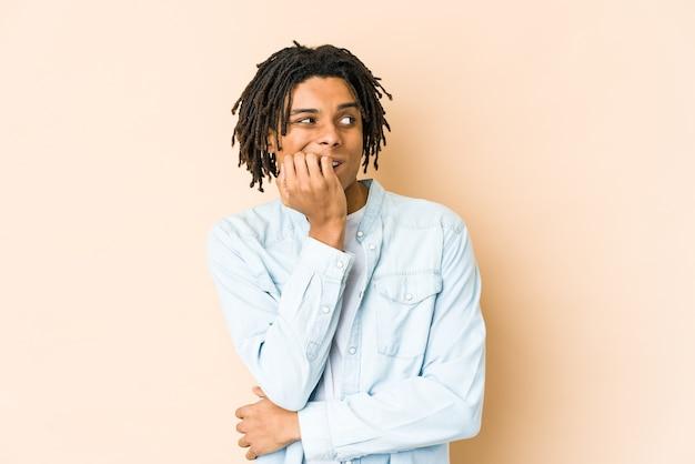 Junger afroamerikaner-rasta-mann beißt fingernägel, nervös und sehr ängstlich.
