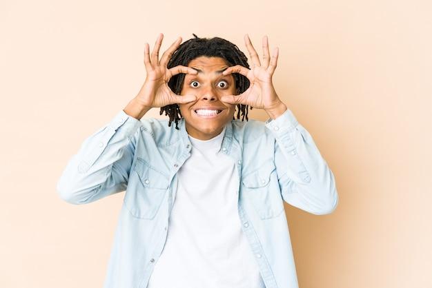 Junger afroamerikaner-rasta-mann, der augen offen hält, um eine erfolgschance zu finden.