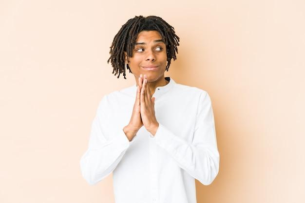 Junger afroamerikaner-rasta-mann, der betet und hingabe zeigt, religiöse person, die nach göttlicher inspiration sucht.