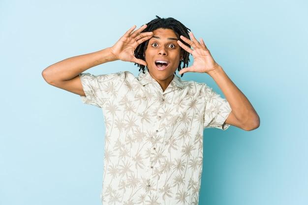 Junger afroamerikaner-rasta-mann, der eine angenehme überraschung empfängt, aufgeregt und hände hebt.