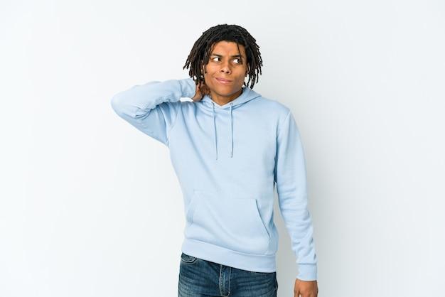 Junger afroamerikaner-rasta-mann, der hinterkopf berührt, denkt und eine wahl trifft.