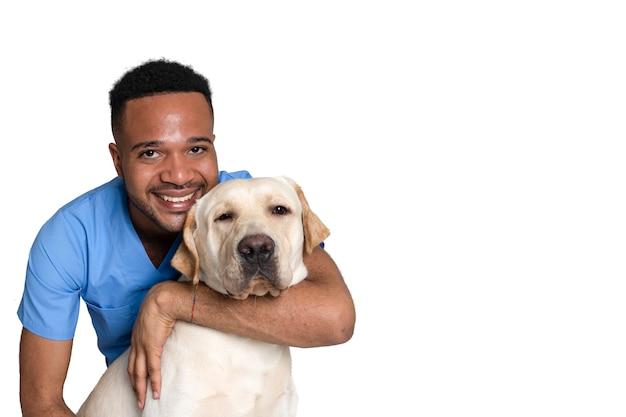 Junger afroamerikaner und schwarzer tierarzt mit einem hund in der klinik