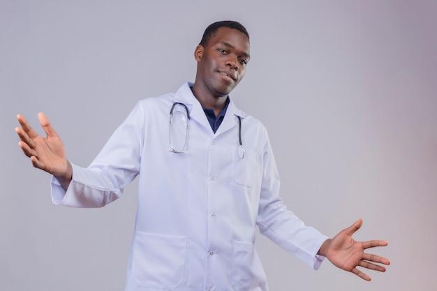 Junger afroamerikanerarzt, der weißen kittel mit stethoskop trägt, das handflächen spreizt, die hand weit öffnen, die einladende geste lächelnd macht
