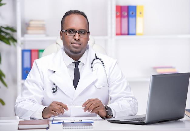 Junger afroamerikanerdoktor sitzt in seinem büro.