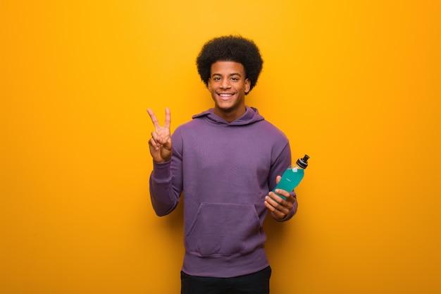 Junger afroamerikanereignungsmann, der einen energiegetränkspaß hält und eine geste des sieges tuend glücklich ist