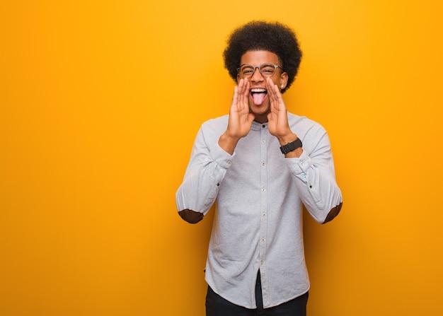 Junger afroamerikanermann auf einer orange wand, die etwas glückliches nach vorne schreit