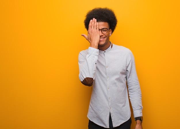 Junger afroamerikanermann auf einer orange wand, die glückliches und kegelndes gesicht mit hand schreit
