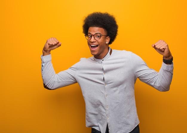 Junger afroamerikanermann auf einer orange wand, die sich nicht ergibt