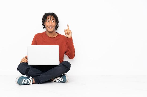 Junger afroamerikanermann, der auf dem boden sitzt und mit seinem laptop arbeitet, der beabsichtigt, die lösung zu realisieren, während er einen finger anhebt