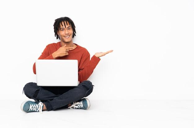 Junger afroamerikanermann, der auf dem boden sitzt und mit seinem laptop arbeitet, der imaginären copyspace auf der handfläche hält, um eine anzeige einzufügen