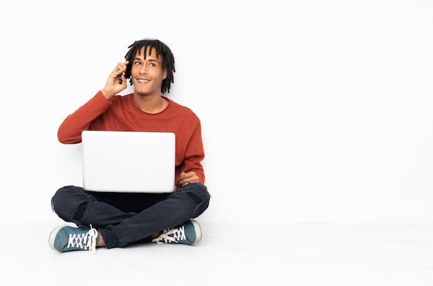 Junger afroamerikanermann, der auf dem boden sitzt und mit seinem laptop arbeitet und ein gespräch mit dem mobiltelefon hält