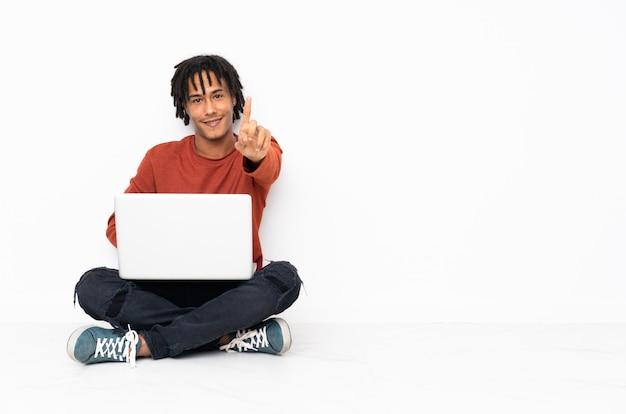 Junger afroamerikanermann, der auf dem boden sitzt und mit seinem laptop arbeitet und einen finger hebt