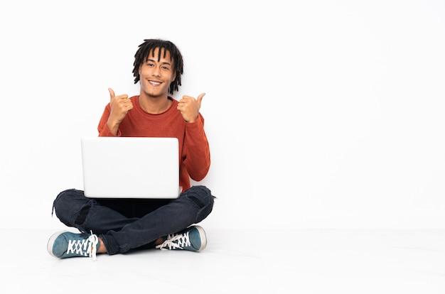 Junger afroamerikanermann, der auf dem boden sitzt und mit seinem laptop mit daumen hoch geste und lächeln arbeitet