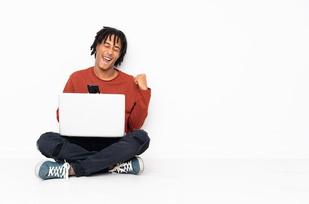 Junger afroamerikanermann, der auf dem boden sitzt und mit seinem laptop mit telefon in der siegposition arbeitet