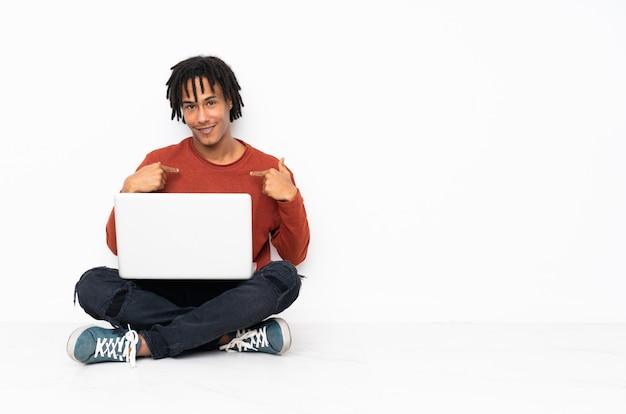 Junger afroamerikanermann, der auf dem boden sitzt und mit seinem laptop mit überraschendem gesichtsausdruck arbeitet