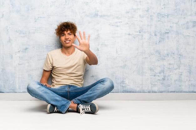 Junger afroamerikanermann, der auf dem boden zählt fünf mit den fingern sitzt