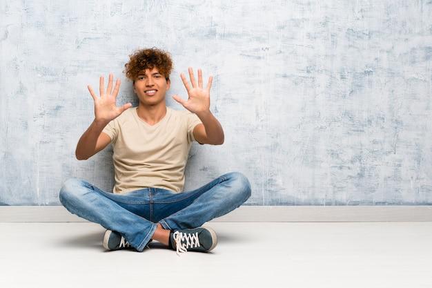 Junger afroamerikanermann, der auf dem boden zählt zehn mit den fingern sitzt