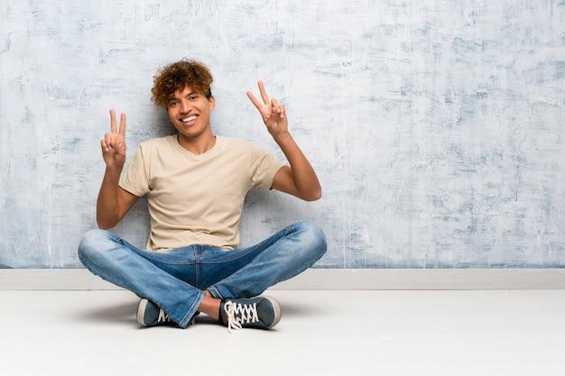 Junger afroamerikanermann, der auf dem boden zeigt siegeszeichen mit beiden händen sitzt