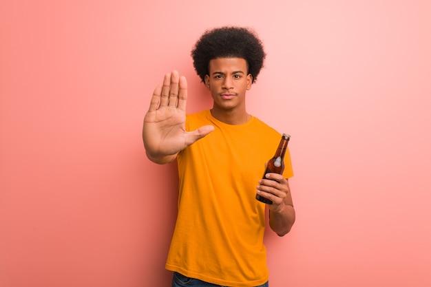 Junger afroamerikanermann, der ein bier hält, das hand vor setzt