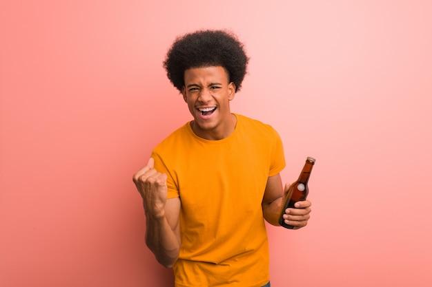 Junger afroamerikanermann, der ein bier überrascht und entsetzt hält